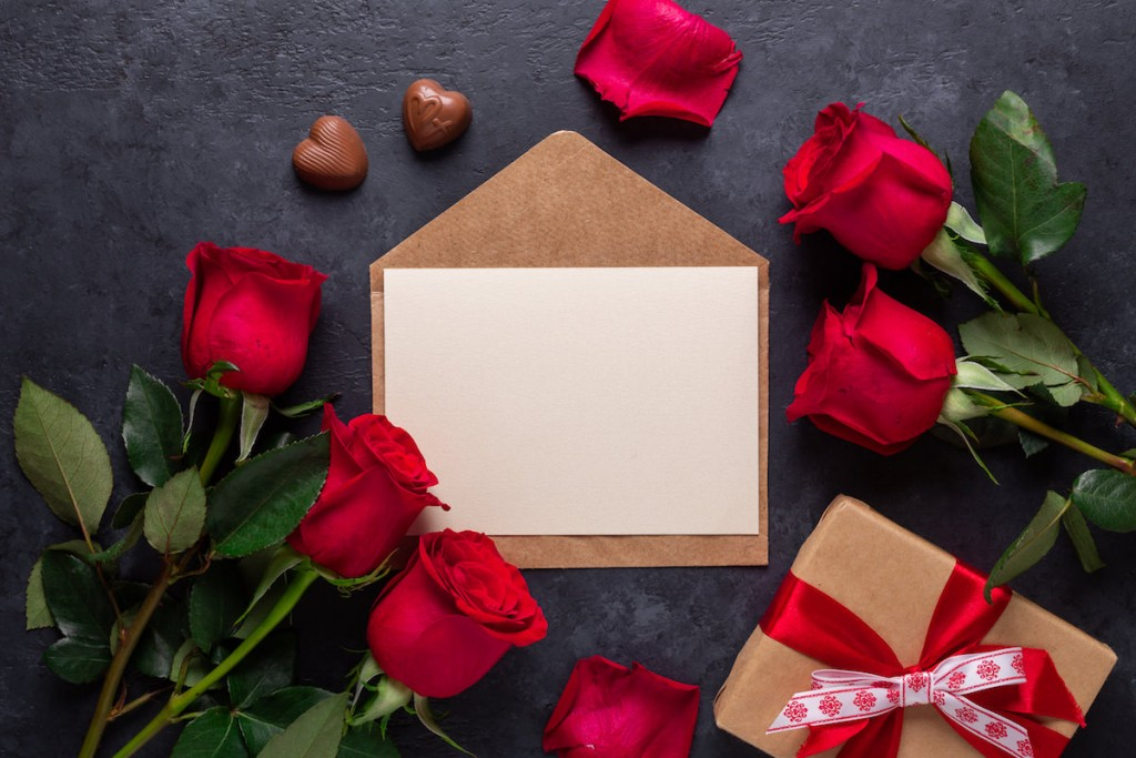 Red rose flowers bouquet, envelope, gift box, chocolate sweets on black stone background Valentine's day greeting card Top view